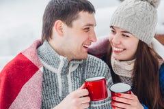 Le unga par med koppar som sitter i snö, parkera Dricka varma drinkar och att ha gyckel arkivfoton