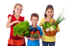Le ungar med nya grönsaker royaltyfria bilder
