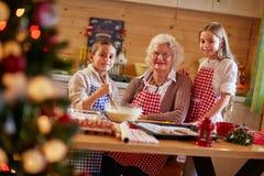 Le ungar som förbereder Xmas-kakor med farmodern royaltyfria bilder