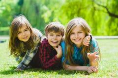Le ungar som har gyckel på gräs Barn som utomhus spelar i sommar tonåringar meddelar utomhus- Royaltyfria Bilder