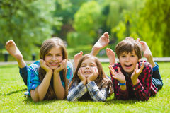 Le ungar som har gyckel på gräs Barn som utomhus spelar i sommar tonåringar meddelar utomhus- Royaltyfria Foton