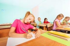 Le ungar som skriver i klassrum under kurs royaltyfria foton
