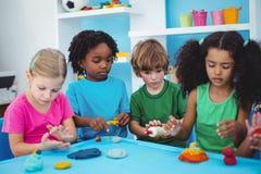 Le ungar som spelar med att modellera lera Royaltyfri Fotografi