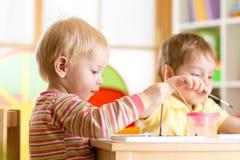 Le ungar som spelar och måla Royaltyfri Bild