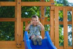 Le ungen som har gyckel på lekplatsen barn som leker utomhus Royaltyfri Fotografi