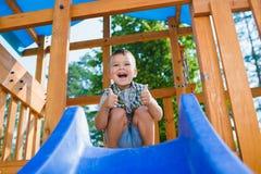 Le ungen som har gyckel på lekplatsen barn som leker utomhus Arkivfoton