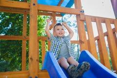 Le ungen som har gyckel på lekplatsen barn som leker utomhus Arkivbilder