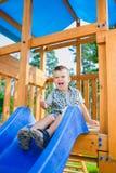 Le ungen som har gyckel på lekplatsen barn som leker utomhus Arkivfoto