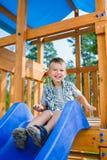 Le ungen som har gyckel på lekplatsen barn som leker utomhus Royaltyfri Foto