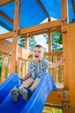 Le ungen som har gyckel på lekplatsen barn som leker utomhus Royaltyfria Foton