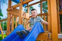 Le ungen som har gyckel på lekplatsen barn som leker utomhus Royaltyfria Bilder