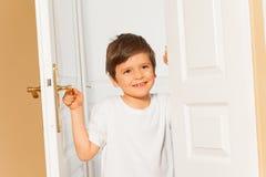 Le ungepojken som hemma öppnar den vita dörren royaltyfria foton