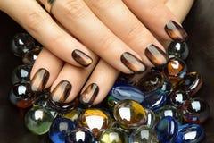 Le unghie della bella donna con il manicure alla moda piacevole fotografie stock