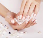 Le unghie della bella donna con il manicure francese Immagine Stock