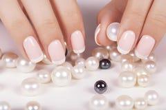 Le unghie della bella donna con il manicure francese Fotografie Stock