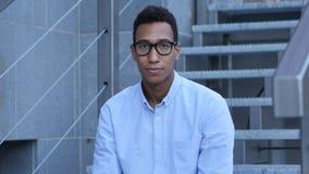 Le ungt svart mansammanträde på trappa, utomhus- stående royaltyfri foto