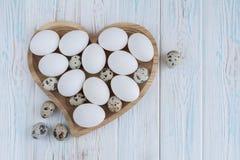 Le uova bianche e le uova di quaglia nel cuore di legno hanno modellato il piatto su fondo bianco di legno Immagini Stock Libere da Diritti