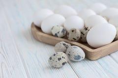 Le uova bianche e le uova di quaglia nel cuore di legno hanno modellato il piatto su fondo bianco di legno Fotografia Stock