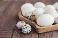Le uova bianche e le uova di quaglia nel cuore di legno hanno modellato il piatto su fondo marrone di legno Fotografie Stock Libere da Diritti