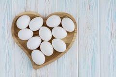 Le uova bianche nel cuore di legno hanno modellato il piatto su fondo bianco di legno Immagine Stock