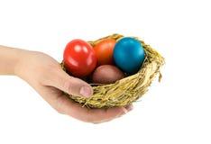 Le uova colorate hanno dipinto la menzogne in un nido naturale sulla palma di una mano femminile Immagini Stock Libere da Diritti