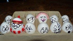 Le uova come caratteri compreso dove è Waldo stanno sedendo in un cartone dell'uovo Fotografia Stock