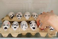 Le uova con le emozioni dipinte nel frigorifero, una mano femminile prende una loro Fotografie Stock Libere da Diritti