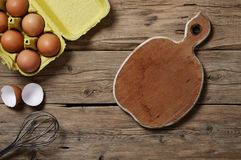 Le uova di Brown con una sbattitura e una cucina imbarcano Fotografia Stock Libera da Diritti