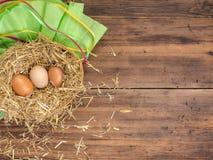 Le uova di Brown in fieno annidano il fondo rurale di eco con le uova e la paglia marroni del pollo sui precedenti di vecchie pla Immagine Stock