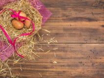 Le uova di Brown in fieno annidano il fondo rurale di eco con le uova marroni del pollo, il nastro rosso e la paglia sui preceden Immagini Stock