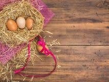 Le uova di Brown in fieno annidano il fondo rurale di eco con le uova marroni del pollo, il nastro rosso e la paglia sui preceden Immagine Stock