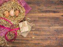 Le uova di Brown in fieno annidano il fondo rurale di eco con le uova marroni del pollo, il nastro rosso e la paglia sui preceden Fotografie Stock Libere da Diritti