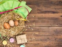 Le uova di Brown in fieno annidano il fondo rurale di eco con le uova marroni del pollo, la paglia, le candele del contenitore di Fotografia Stock
