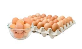 Le uova di Brown nella ciotola di vetro e nel cartone egg il vassoio Fotografia Stock