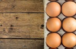 Le uova di gallina in polpa marrone modellano il pacchetto del vassoio sulla tavola di legno Immagini Stock Libere da Diritti