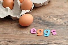 Le uova di parola visualizzate con il pollo eggs in una scatola delle uova Immagine Stock Libera da Diritti