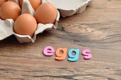 Le uova di parola visualizzate con il pollo eggs in una scatola delle uova Fotografia Stock