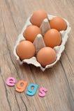 Le uova di parola visualizzate con il pollo eggs in una scatola delle uova Immagini Stock Libere da Diritti