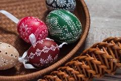 Le uova di Pasqua casalinghe e fatte a mano sulla betulla si ramifica sul vassoio di legno, Ceco tradizionale, la caccia dell'uov immagine stock