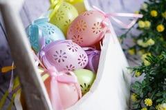 Le uova di Pasqua colorate del pizzo con il nastro si piegano in canestro di legno bianco fotografie stock libere da diritti