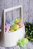Le uova di Pasqua colorate del pizzo con il nastro si piegano in canestro di legno bianco immagini stock