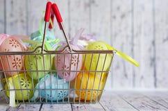 Le uova di Pasqua colorate del pizzo con il nastro si piegano in cestino della spesa Immagini Stock