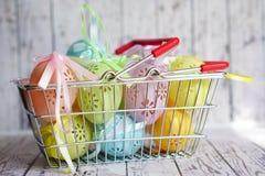 Le uova di Pasqua colorate del pizzo con il nastro si piegano in cestino della spesa Fotografia Stock