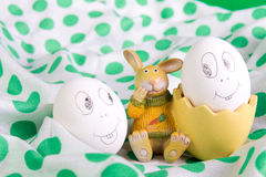 Le uova di Pasqua con i fronti divertenti si avvicinano al coniglietto Fotografia Stock Libera da Diritti