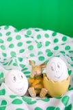 Le uova di Pasqua con i fronti divertenti si avvicinano al coniglietto sulla tovaglia del pois Fotografia Stock