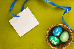 Le uova di Pasqua con i modelli si trova sui vecchi precedenti di legno con la carta in bianco Fotografia Stock Libera da Diritti