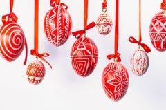 Le uova di Pasqua con il modello ucraino piega appendono sui nastri rossi su fondo bianco Fotografia Stock Libera da Diritti