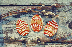 Le uova di Pasqua con il salice si ramifica su un fondo di legno Fotografia Stock
