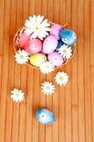 Le uova di Pasqua decorate con le margherite hanno pieghettato dentro un canestro Immagine Stock
