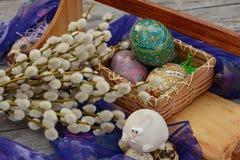 Le uova di Pasqua decorate si avvicinano al salice ed al coniglietto di pasqua Fotografia Stock Libera da Diritti